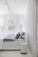 Bett mit grauer Bettwäsche und rundem Rollcontainer als Nachtkästchen vor bodenlangem Vorhang in weissem Schlafzimmer