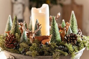 Christmas arrangement of small fir trees, animal figurines and white pillar candle
