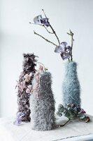 Vasen in gestrickten und gehäkelten Hüllen; getrocknete Blüten