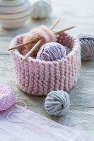 Aus rosa Wolle gestricktes Körbchen mit Wollresten und Stricknadeln
