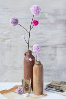 Hand-made, artificial, lilac pompom flowers in stoneware vases