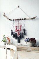 Wandschmuck mit Birkenast und aufgehängten DIY-Quasten aus Wollresten