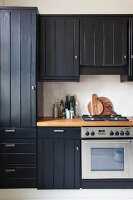 Black country-house kitchen with wooden board doors