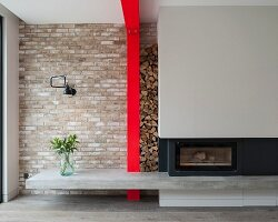 Modern fireplace with concrete hearth, firewood stacked between grey chimney breast and red steel column against brick wall