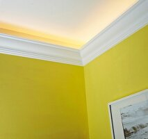 Indirect lighting secreted above white DIY stucco moulding on yellow walls