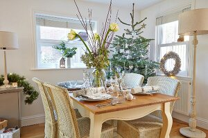 Vase of flowers on set table in rustic dining room with decorated Christmas tree in corner