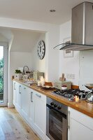 Long wooden kitchen worksurface with extractor hood above gas cooker