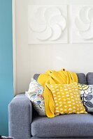 Colourful scatter cushions and blanket on grey sofa