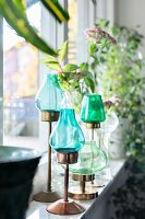 Candle lanterns with blue and green glass shades on windowsill