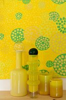 Yellow glass vases in front of yellow artworks with motif of circles