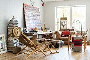 Folding armchair with wooden frame and matching footstool in eclectic, artistic living room