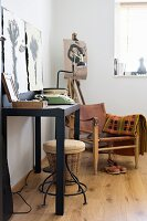 Black console table and armchair with leather seat and backrest in corner of artistic interior