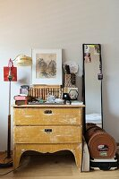 Clutter of objects on top of chest of drawers between standard lamp and narrow full-length mirror