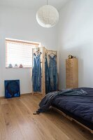 Bed with dark blue bed linen and dungarees hung from wooden screen next to window in minimalist interior