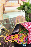 Strings of colourful plastic beads spilling out of open tin and lampshade frames made from pastel wire on tabletop