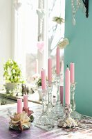 Pink candles in romantic candlesticks on table in front of window