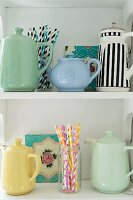Collection of teapots and coffee pots and colourful drinking straws on white shelves