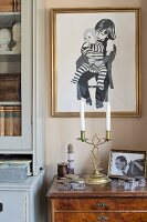 Black and white picture of children in gilt frame above white candles in brass candlesticks on top of antique chest of drawers