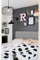 Double bed with upholstered headboard and black and white polka-dot bed linen below decorative letters on dark grey wall