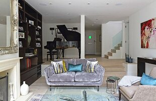 Grey velvet sofa in lounge area; black grand piano on dais in background