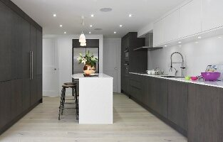 Fitted kitchen with dark brown cupboards, white island counter, recessed spotlights and white wall cabinets in elegant interior