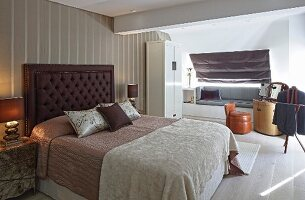 Double bed with button-tufted headboard against striped wallpaper in elegant bedroom