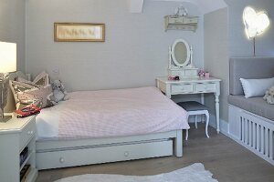 Romantic dressing table next to bed with pale pink bed linen in girl's bedroom