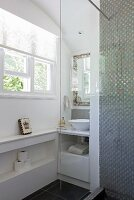View of washstand in niche next to window seen from shower area