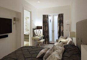 Elegant double bed with dark brown bedspread and arranged scatter cushions and dressing table in front of French windows