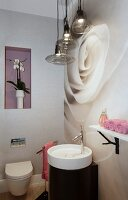 Feminine guest toilet with round sink against wall with photo mural of huge white rose