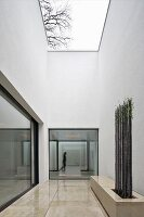 House with atrium, minimalist patio and stone bench with trellising under cloudy sky