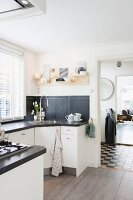 Kitchen with white polygonal counters and black worksurface