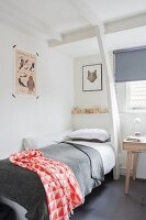 Single bed with red and white patterned blanket in corner below white wooden structure
