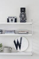 Retro cameras, CD cases and black and white decorative plate on white String shelves