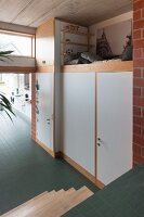 Fitted cupboards and loft bed in industrial loft apartment