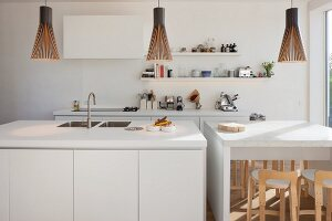 White island counter and breakfast bar below pendant lamps in open-plan kitchen