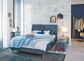 Double bed with denim-upholstered frame in bedroom with blurred patterns on wallpaper and rug