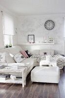 White corner couch, matching ottoman and shabby-chic side table in corner of living room