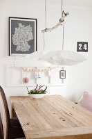 Kette aus Holzkugeln an weissem Bilderrahmen, davor rustikaler Holztisch mit Blumenschale und Pendelleuchte