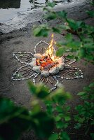 Romantic campfire on river bank surrounded by flower pattern of stones and sticks
