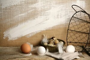 Hens' eggs, quail's eggs, feathers and wire basket