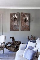 Arrangement of old shutters and candle sconces on wall