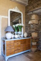 Vase of white flowers and table lamp in front of mirror on top of chest of drawers next to rustic stone wall