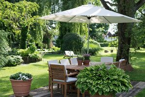 Parasol integrated in garden table and wooden chairs with white cushions in summer garden