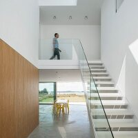 Staircase with glass balustrade in minimalist interior with dining table in front of sliding terrace doors in background
