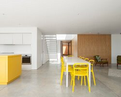 Minimalist interior with concrete floor, kitchen and dining area in yellow and white
