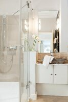 Shower with glass partition and washstand with white base unit in modern bathroom