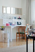 Desk with white drawer unit on top against wall, retro armchair and silver metal waste paper basket