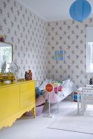 Yellow-painted sideboard and white child's bed against patterned wallpaper