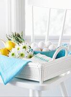 Eier, Spargel, Zitronen und Blumen im Korb auf weissem Stuhl